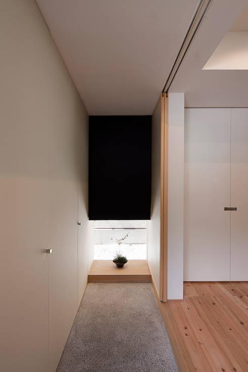 地窓を飾り棚とした玄関: 根來宏典建築研究所が手掛けた廊下 & 玄関です。