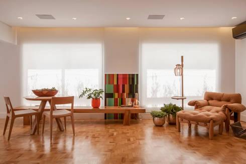 Bar e Poltrona de leitura: Salas de estar ecléticas por Helô Marques Associados