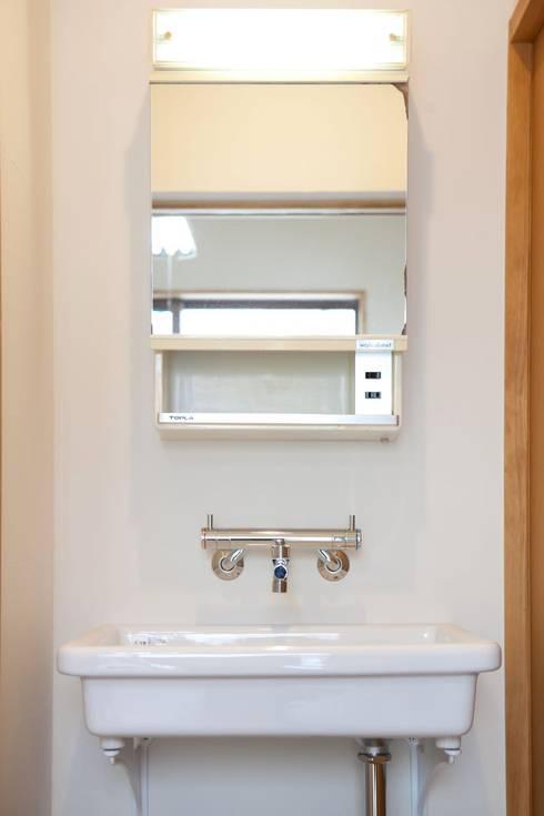 洗面鏡もレトロ: アトリエdoor一級建築士事務所が手掛けた浴室です。