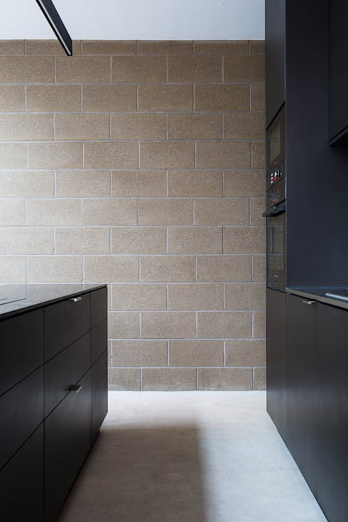 View of exposed block work wall between kitchen island and main run of units: industrial Kitchen by Mustard Architects
