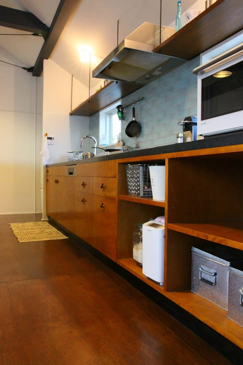 玄関土間の薪ストーブが家全体を暖める: HOUSETRAD CO.,LTDが手掛けたキッチンです。