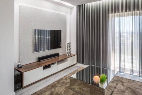A sala do Pedro: Sala de estar  por Cássia Lignéa
