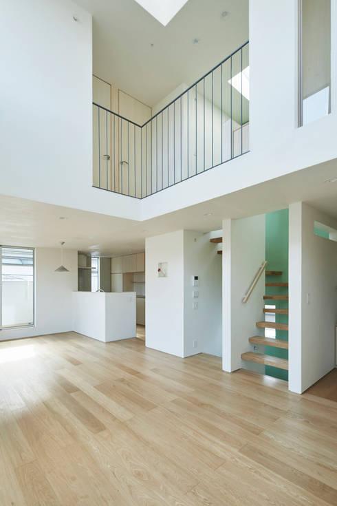 要町の家 吹抜けを通して光が溢れる家: エトウゴウ建築設計室が手掛けたリビングです。