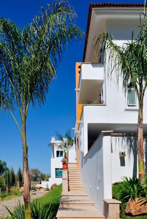 ingreso de costado: Casas de estilo colonial por Excelencia en Diseño