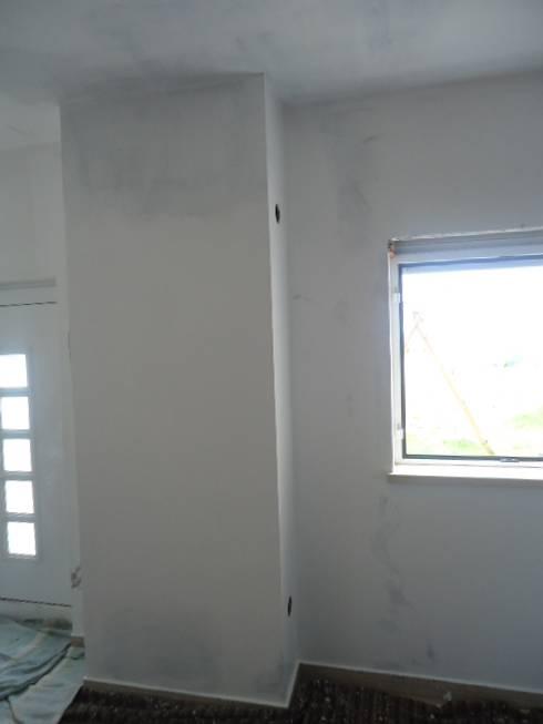 Reparação de infiltrações, pintura de tecto e paraedes na cor branco em cave de moradia (durante a obra):   por Atádega Sociedade de Construções, Lda