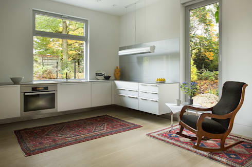 Modern floating kitchen with glass backsplash: modern Kitchen by ZeroEnergy Design