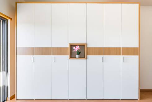 Roupeiro com portas articuladas: Vestiário  por GenesisDecor