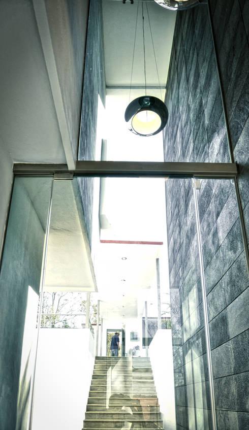 DOBLE ALTURA EN ACCESO: Pasillos y recibidores de estilo  por ArqCubo