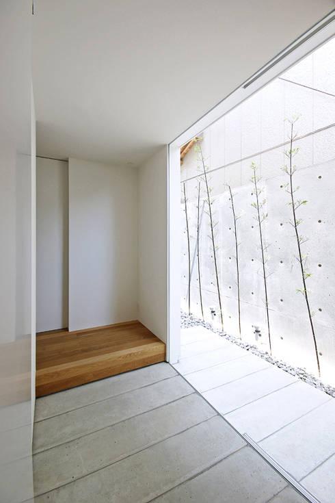 玄関、坪庭: 空間建築-傳 一級建築士事務所が手掛けた廊下 & 玄関です。