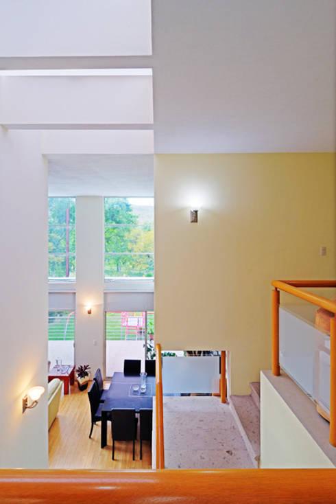 DOBLE ALTURA: Pasillos y recibidores de estilo  por Excelencia en Diseño