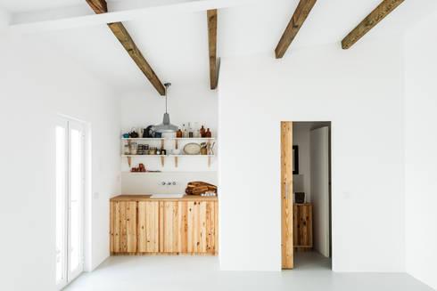 Vista da zona de copa e instalação sanitária: Cozinhas rústicas por Arkstudio