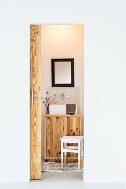 Detalhe do conjunto do lavatório, instalação sanitária: Casas de banho rústicas por Arkstudio