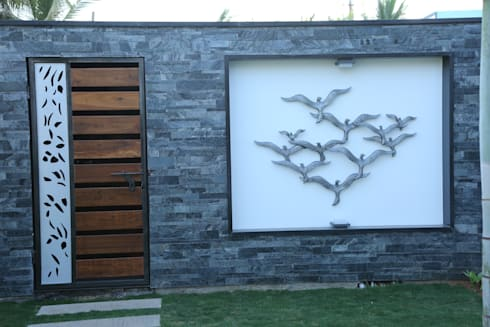 garden area wall with stone cladding and a bird mural: modern Houses by Hasta architects
