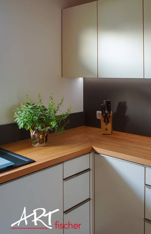 Küchenarbeitsplatte mit Nischenrückwand und integierter Beleuchtung:  Küche von ARTfischer Die Möbelmanufaktur.