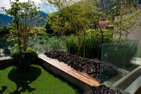 Jardim na cobertura, com grama e vegetação. : Jardins modernos por Oswaldo Magalhães Filho - PAAL