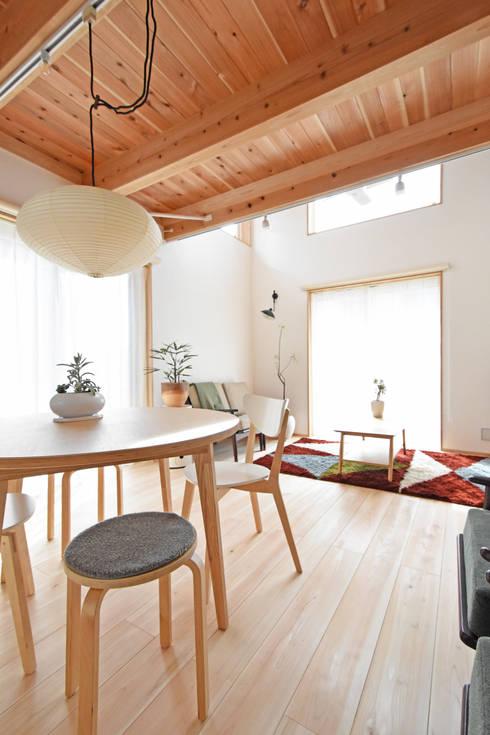 光の差し込む大窓と吹き抜け空間: 合同会社negla設計室が手掛けたリビングです。