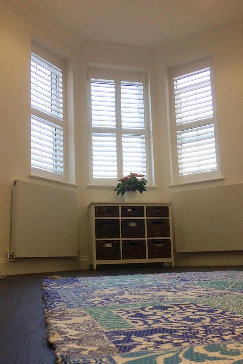 Bedroom shutters for bay windows: classic Bedroom by Plantation Shutters Ltd