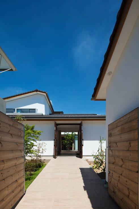 門から玄関、中庭、LDKを見通す: 株式会社seki.designが手掛けた家です。