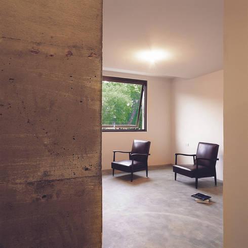 東側包覆臥室起居的厚牆,是利用水泥灌鑄來整合原承重結構,藉牆面的彎摺,埋入生活伏筆。:  客廳 by 本晴設計