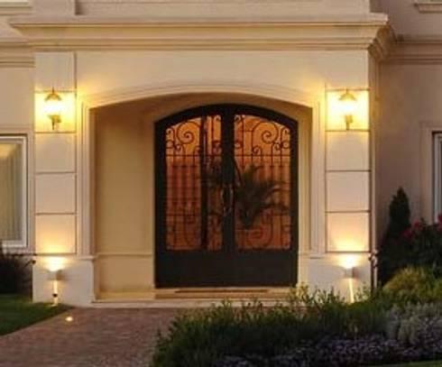Puerta de hierro con cabezal curvo. : Casas de estilo clásico por Del Hierro Design