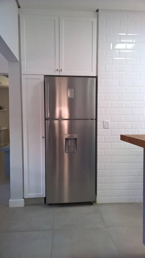 Detalhe para armário embutido | geladeira, despensa e um detalhe para a parede de brich liverpool da portobello: Cozinhas  por R.E. Projetos