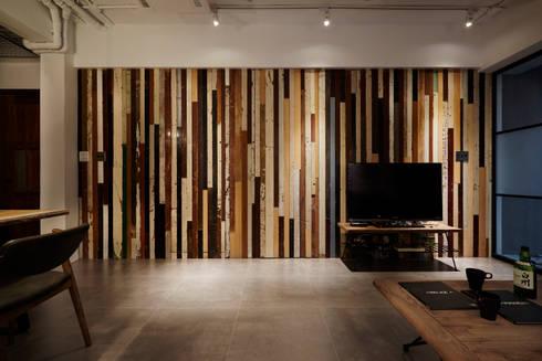 使用大量實木舊廢料隱藏主臥室及浴室的入口,捨棄傳統電視牆的設定讓電視被牆延伸,展延視覺的長度:  客廳 by 弘悅國際室內裝修有限公司