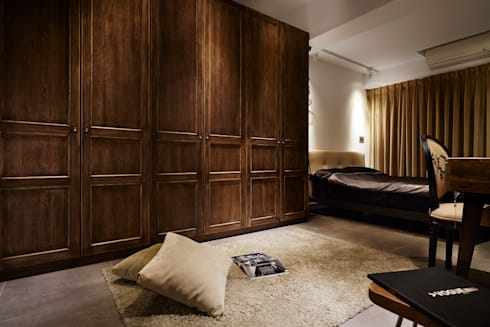 衣櫃使用傳統的古典線版,採用仿舊的就化處理,在粗獷的空間中帶點溫暖精緻的點綴:  臥室 by 弘悅國際室內裝修有限公司