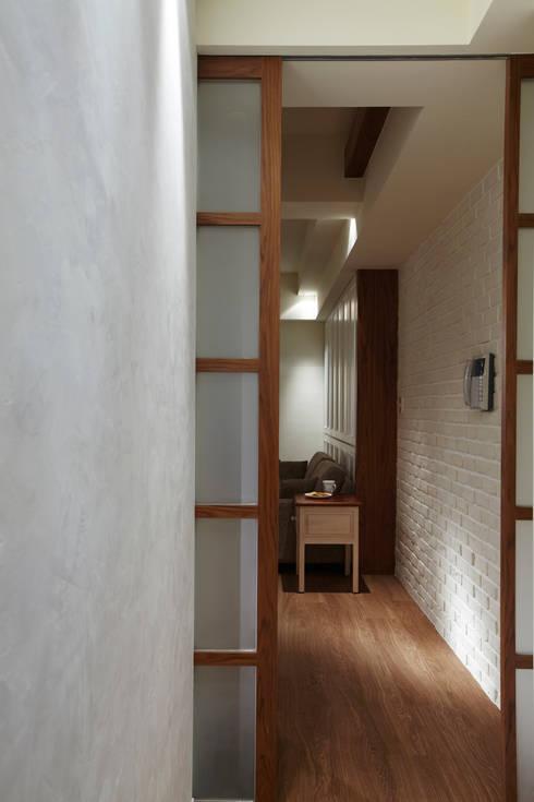 建物本身狹長的廊道利用玻璃拉門遮掩起來,一是減少空間廊道的陰暗感,二來增加居家生活的私密性:  走廊 & 玄關 by 弘悅國際室內裝修有限公司