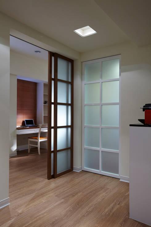 透過不同顏色的門片增加空間的趣味,而引進戶外的光線也增加室內的通透感:  書房/辦公室 by 弘悅國際室內裝修有限公司