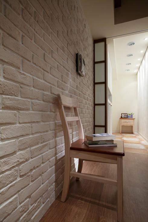 磚牆的紋理一直有令人說不出的溫暖,簡單而具有質感:  走廊 & 玄關 by 弘悅國際室內裝修有限公司