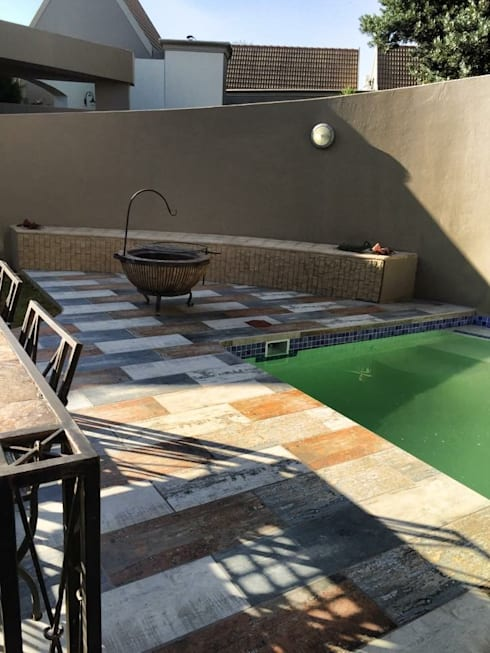 Simple firepit seating alongside pool:  Patios by Acton Gardens