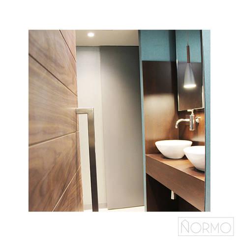 Candeeiro suspenso em metal com pormenor em madeira: Casa de banho  por Normo