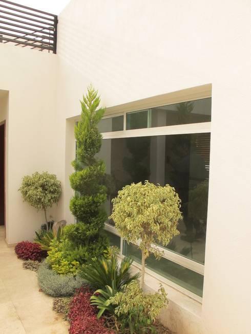 Fachada interior cochera: Casas unifamiliares de estilo  por ÖQ Arquitectos