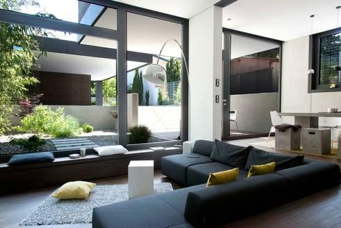 Offener Wohnbereich mit Blick zum Garten und Garage: moderne Wohnzimmer von Herrmann Massivholzhaus GmbH