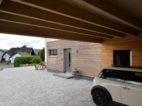 Carport: moderne Garage & Schuppen von Herrmann Massivholzhaus GmbH