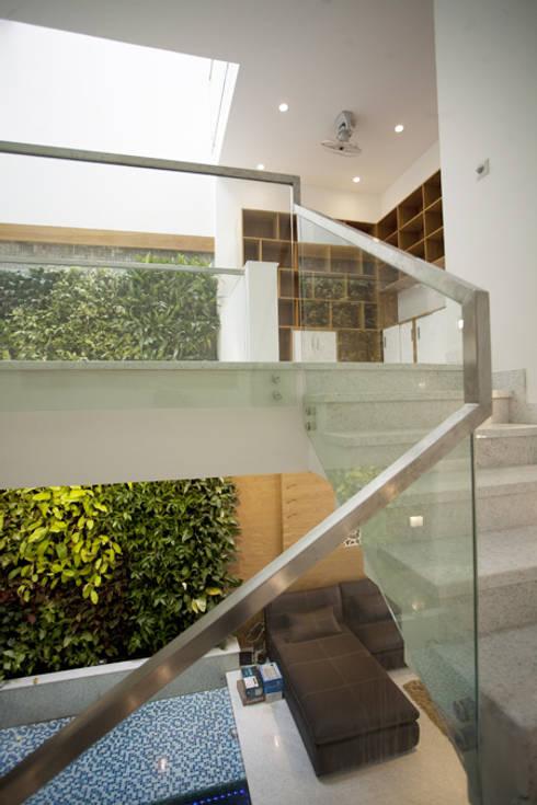Cầu thang được thiết kế tay vịnh bằng vật liệu kính sang trọng.:  Cầu thang by Công ty TNHH Thiết Kế Xây Dựng Song Phát