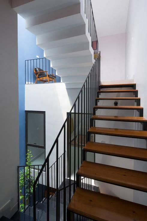 Cầu thang thiết kế bằng sắt với mặt bậc ốp gỗ giúp nhẹ kết cấu và tăng độ thông thoáng.:  Cầu thang by Công ty TNHH Thiết Kế Xây Dựng Song Phát