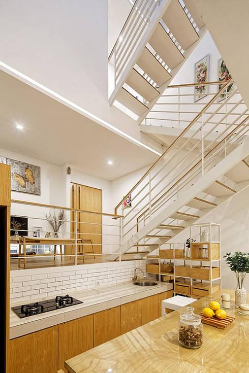 Phòng bếp và bàn ăn được bố trí ở ngay cạnh cầu thang.:  Bếp xây sẵn by Công ty TNHH Thiết Kế Xây Dựng Song Phát