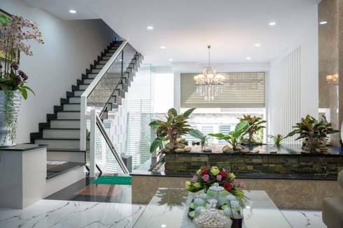 Không gian mở giữa phòng khách và bếp ăn:  Phòng khách by Công ty TNHH Xây Dựng TM – DV Song Phát
