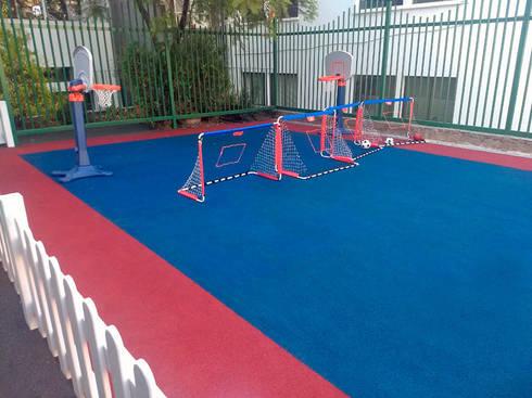 Caucho in situ patio de juegos sección kinder de colegio: Escuelas de estilo  por Constructora Las Américas S.A.