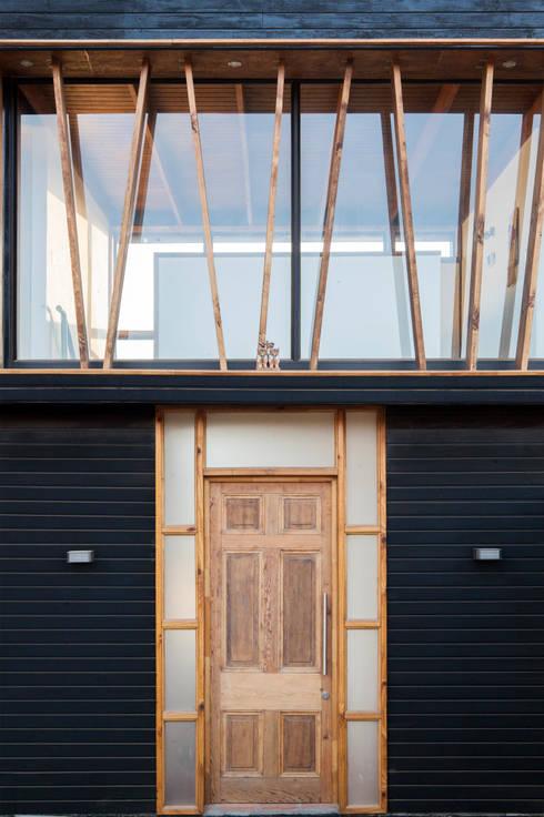 PUERTA PRINCIPAL DE MADERA  RECICLADA: Puertas de madera de estilo  por arquiroots
