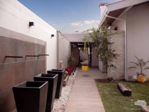 ÁREA DE LAZER COM FONTE: Corredores e halls de entrada  por THACO. Arquitetura e Ambientes