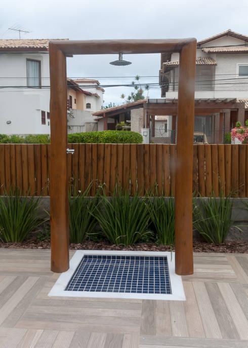 Muro de madeira e paisagismo criam barreira natural para a piscina: Condomínios  por Bernal Projetos - Arquitetos em Salvador