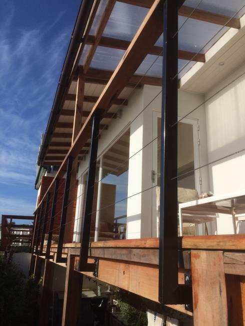 Detalle baranda con pasamanos de roble y tensores de acero inoxidable: Casas unifamiliares de estilo  por Lares Arquitectura