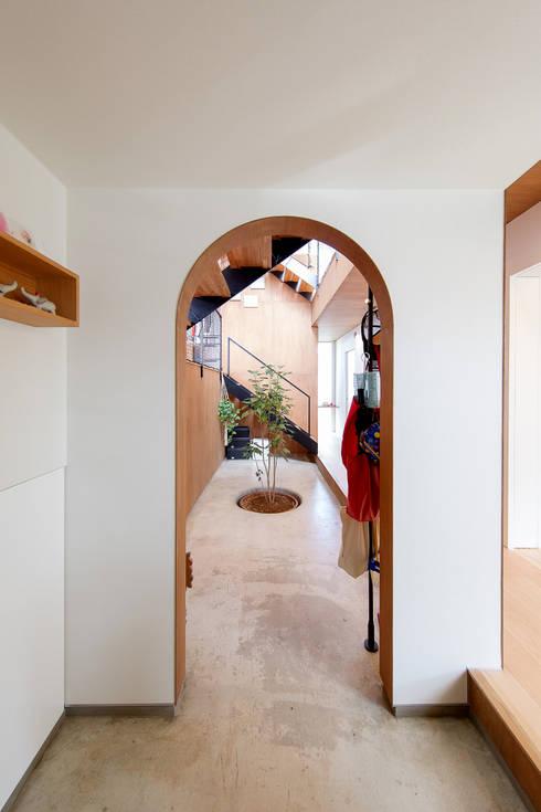 家の中にある土間ホールへの入り口: 株式会社建築工房DADAが手掛けた廊下 & 玄関です。