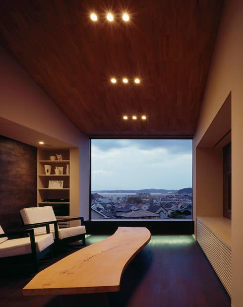 リビング(夕景): 松岡淳建築設計事務所が手掛けたリビングです。