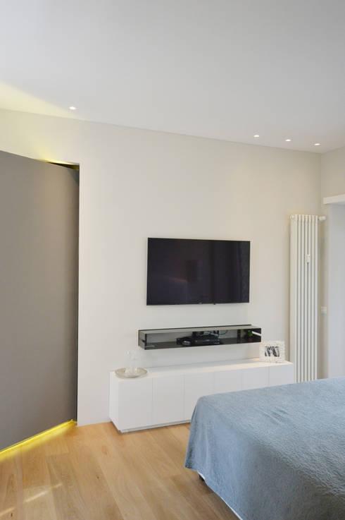 Camera da letto con parete TV: Camera da letto in stile  di odap - arch. matteo pavese