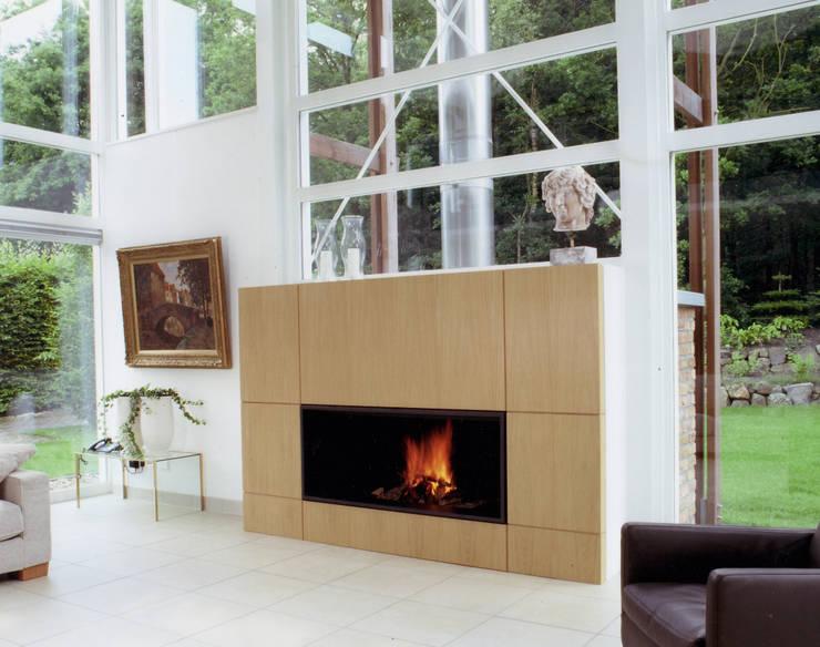 cheminée murale en metal et bois: Salon de style  par Bloch Design