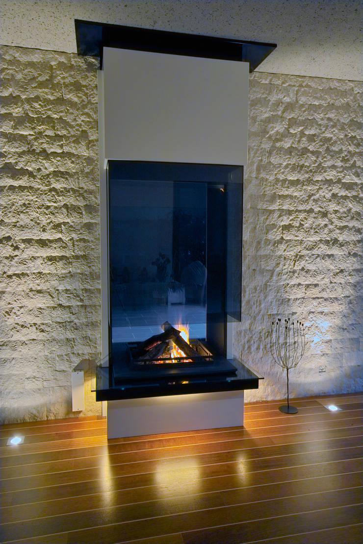 cheminée double face: Salon de style  par Bloch Design
