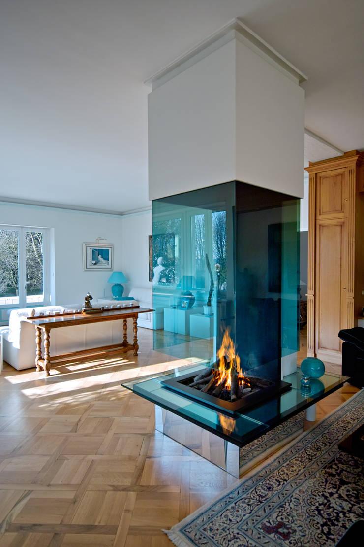 Cheminée moderne en verre et metal: Salon de style  par Bloch Design